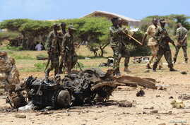 Jubaland forces walk near the site of a suicide car bomb attack near a military training base in the port town Kismayu, south of capital Mogadishu August 22, 2015. A suicide car bomb was rammed into a military training base in the Somali port city of