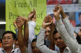 Members of the opposition Cambodia National Rescue Party raise joined hands for photographs at their party headquarters in Phnom Penh, May 27, 2016. A Cambodian court had convicted three military commandos of beating up two CNRP lawmakers outside the...
