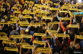 """People hold banners reading """"Freedom Political Prisoners"""" gather in support of the members of the dismissed Catalan cabinet after a Spanish judge ordered the former Catalan leaders to be remanded in custody pending an investigation into Catalonia's i"""