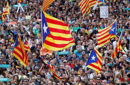 People wave Catalan separatist flags during a demonstration organised by Catalan pro-independence movements ANC (Catalan National Assembly) and Omnium Cutural, following the imprisonment of their two leaders Jordi Sanchez and Jordi Cuixart,  in Barce...