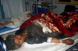 Injured Afghan villagers lie on beds in a hospital ward in Farah Province after they were caught in an explosion of a roadside bomb, November 16, 2012.