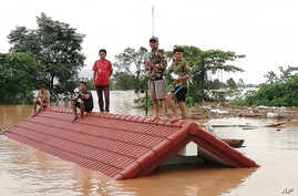 Villagers take refuge on a rooftop above flood waters from a collapsed dam in the Attapeu district of southeastern Laos, July 24, 2018.