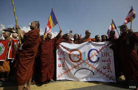 Buddhist monks hold a banner as they protest against the opening of Organization of Islamic Cooperation (OIC) offices in Burma, in front of the city hall in Rangoon, October 15, 2012.