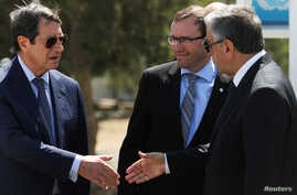 Greek Cypriot leader and Cyprus President Nicos Anastasiades (L) shake hands with Turkish Cypriot leader Mustafa Akinci (R), as UN envoy Espen Barth Eide looks on, in the buffer zone of Nicosia airport, Cyprus, Sept. 14, 2016.