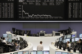 Traders work at their desks in front of the DAX board at the Frankfurt stock exchange, May 14, 2012.