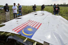 Malaysian investigators along with members of the OSCE mission in Ukraine, examine a piece of the crashed Malaysia Airlines Flight 17 in the village of Petropavlivka, Donetsk region, eastern Ukraine, July 23, 2014.