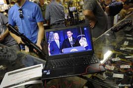 Gun shop customers shop for weapons at the Bullet Hole gun shop in Sarasota, Florida, as they listen to live streaming video of an announcement about gun control by U.S. President Barack Obama, January 16, 2013. Obama proposed a new assault weapons b
