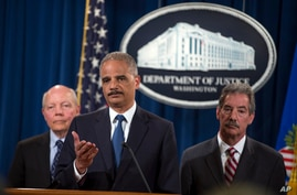IRS Commissioner John Koskinen, left, and Deputy Attorney General James Cole, right, watch as Attorney General Eric Holder speaks during a news conference at the Justice Department, on Monday, May 19, 2014, in Washington