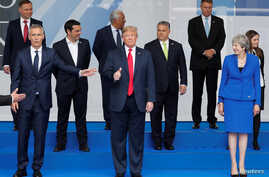 U.S. President Donald Trump gestures as NATO leaders pose for a family photo at the start of the NATO summit in Brussels, Belgium