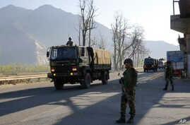 An Indian army soldier stands guard as an army convoy moves on a highway on the outskirts of Srinagar, Indian-controlled Kashmir, Feb. 7, 2019.