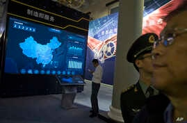 FILE - Visitors look at a display of information technologies at an exhibition highlighting China's achievements under President Xi Jinping's leadership, at the Beijing Exhibition Hall in Beijing, China, Oct. 17, 2017.