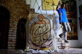 """Cuban artist Italo Esposito, a participant of the """"00Biennial"""", walks in his home next to his work in Havana, Cuba, May 2, 2018."""