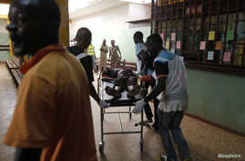 People escort a wounded civilian at the community hospital in Bangui, Feb. 19, 2014.