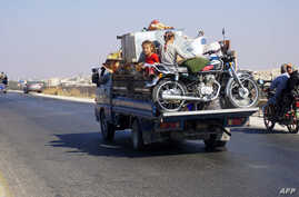 Syrian children ride in the back of a truck loaded with furniture and a motorcycle, driving along the main Damascus-Aleppo highway near the town of Saraqib in Syria's mostly rebel-held northern Idlib province, as families flee north from the countrys