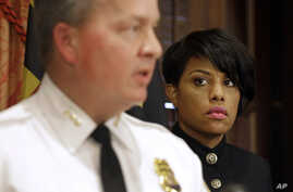 After announcing the firing of Police Commissioner Anthony Batts, Baltimore Mayor Stephanie Rawlings-Blake listens as Interim Commissioner Kevin Davis talks to reporters in Baltimore, July 8, 2015.