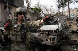 A U.S. soldier stands at the site where a suicide bomber attacked a police compound in Surobi district of Kabul, Afghanistan,  Feb. 21, 2014.