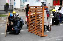 Protester shield themselves from police during a May Day demonstration in Istanbul, May 1, 2014.