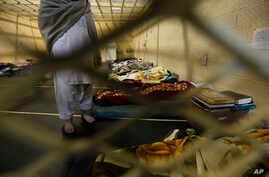 FILE - Afghan detainees are through mesh wire fence inside the Parwan detention facility near Bagram Air Field in Afghanistan.