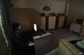 FILE - A man uses a computer at an internet cafe in Rawalpindi, Pakistan, Sept. 18, 2013