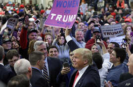 Republican presidential candidate Donald Trump holds up a sign handed to him by a supporter after speaking at a campaign rally  in Bethpage, New York, April 6, 2016.