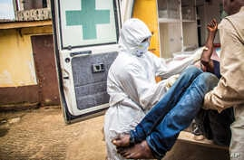 FILE- Health workers load a suspected Ebola patient into the back of an ambulance in Freetown, Sierra Leone, Sept. 24, 2014.