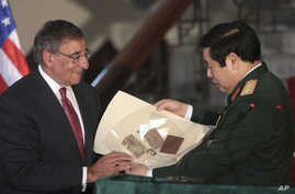 U.S. Defense Secretary Leon Panetta, left, gives a Vietnam War memorabilia of a Vietnamese soldier, which was kept by the U.S., to his Vietnamese counterpart Phung Quang Thanh during a joint press conference at Ministry of Defense in Hanoi, Vietnam,