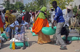 FILE - Somali internally displaced people receive food aid donated by a Qatari charity during the holy Muslim month of Ramadan in Mogadishu, June 20, 2015. Somalia's federal government has said it will stay neutral in Qatar's dispute with other Gulf
