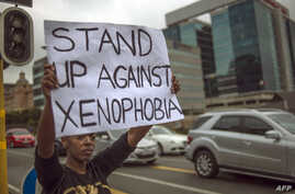 A South African holds a sign as she stands on the side od a road in Sandton, as xenophobic violence continued, on April 18, 2015.