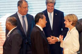 Russia's Foreign Minister Sergey Lavrov, U.S. Secretary of State John Kerry, rear, stand with India's Minister of External Foreign Affairs General V.K. Singh, left, China's Foreign Minister Wang Yi, center, and Australia's Foreign Minister Julie Bish