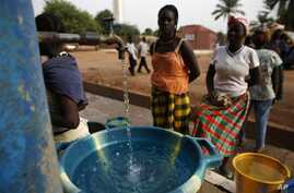 Girls fill plastic basins at a free water tap in a neighborhood where houses with indoor plumbing rarely receive water, in Bissau, Guinea-Bissau (2009 photo)