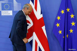 FILE - A worker arranges flags at the EU headquarters as Britain and the EU launch Brexit talks in Brussels, June 19, 2017.