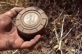 In this still image made from video taken Sept. 7, 2015 provided by the Syrian Center for Demining and Rehabilitation, a volunteer deminer takes a landmine from the ground in Daraa, Syria.