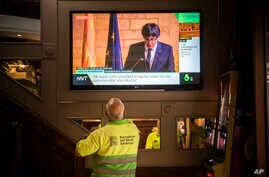 People in a bar watch the speech of Catalan regional president Carles Puigdemont on television in Barcelona, Spain, Thursday, Oct. 26, 2017.