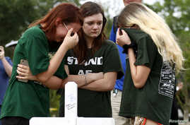 Mourners gather at a makeshift memorial left in memory of the victims killed in a shooting at Santa Fe High School in Santa Fe, Texas, U.S., May 21, 2018.