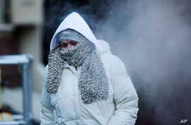 A commuter walks along Market Street in freezing temperatures Tuesday, Nov. 18, 2014, in Philadelphia.