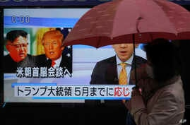 "A woman walks past a public TV screen showing North Korean leader Kim Jong Un, left, and U.S. President Donald Trump in Tokyo, March 9, 2018. The signs read: ""Trump has accepted an offer of a summit from the North Korean leader and will meet with Kim"