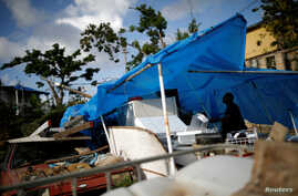 Joe Quirindongo tries to repair a makeshift tent where he keeps some belongings at the squatter community of Villa Hugo in Canovanas, Puerto Rico, Dec. 9, 2017. Villa Hugo is a settlement initially formed by people whose houses were damaged or destro