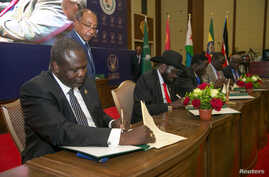 South Sudanese rebel leader Riek Machar, left, and South Sudan's President Salva Kiir sign a ceasefire and power sharing agreement in Khartoum, Sudan, Aug. 5, 2018.