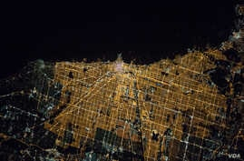 """Expedition 47 Commander Tim Kopra of NASA captured this brightly lit night image of the city of Chicago on April 5, 2016, from the International Space Station. Kopra (@astro_tim) wrote, """"#Goodnight #Chicago from @Space_Station. #CitiesFromSpace"""""""