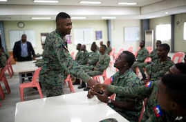 A member of Haiti's new national military force greets a fellow soldier in a meeting room at a former U.N. base in Gressier, Haiti,  April 11, 2017.