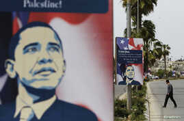 Palestinian man walks near placards designed by an activist depicting U.S. President Barack Obama, ahead of his visit to the region, in the West Bank city of Ramallah, Mar. 12, 2013.
