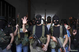 Shi'ite masked gunmen from the Mekdad clan gather at the Mekdad family's association headquarters in the southern suburbs in Beirut, Lebanon, August 15, 2012.
