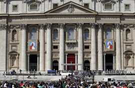 The tapestries showing late Pope John Paul II and Pope John XXIII hang from the facade of St. Peter's Basilica as faithful and pilgrims crowd St. Peter's Square, Apr. 25, 2014.