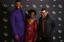 FILE - Actors Winston Duke, from left, Lupita Nyong'o and director Jordan Peele pose for photographers upon arrival at the premiere of the film 'Us' in London, March 14, 2019.