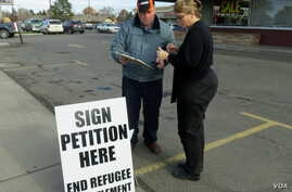 Marie Christopherson of Buhl, Idaho, stopped to sign Rick Martin's petition to ban refugee centers in Twin Falls County.