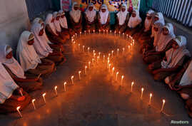School girls light candles in the shape of a ribbon during a HIV/AIDS awareness campaign ahead of World Aids Day, in Ahmedabad, India, Nov. 30, 2016.