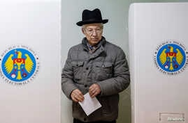 A man leaves a booth before casting his vote during a presidential election at a polling station in Chisinau, Moldova, Oct. 30, 2016.