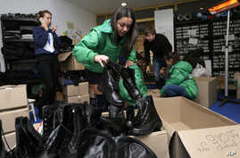 Ukrainian volunteers packing military boots to be sent to government soldiers waging combat against pro-Russian separatists in eastern Ukraine in Kyiv, Friday, Nov. 14, 2014.