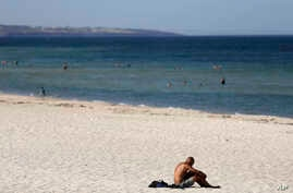 A beachgoer sits in the sun on Glenelg Beach in Adelaide, Australia, Jan. 24, 2019.