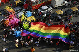 FILE - Participants holding a rainbow flag pass through a junction during a gay pride parade, which is promoting gay, lesbian, bisexual and transgender rights, in Mumbai, Jan. 31, 2015.
